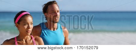 Couple runners running on beach. Young adults asian woman, caucasian man, training cardio together doing outdoor workout jogging. Panorama horizontal banner crop for copy space.