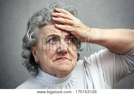 Old grandmother headache on a grey background