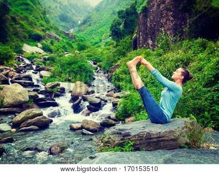 Yoga exercise outdoors - woman doing Ashtanga Vinyasa Yoga balance asana Ubhaya padangusthasana Big Double Toe Yoga Pose at waterfall in Himalayas in India. Vintage retro filtered hipster style image.