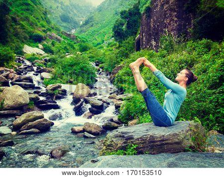 Yoga exercise outdoors - woman doing Ashtanga Vinyasa Yoga balance asana Ubhaya padangusthasana Big Double Toe Yoga Pose at waterfall in Himalayas in India. Vintage retro filtered hipster style image.