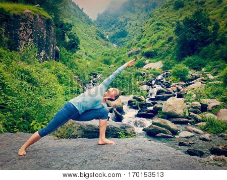 Sporty fit woman practices yoga asana Utthita Parsvakonasana -  extended side angle pose outdoors at water. Vintage retro effect filtered hipster style image.