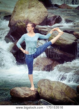 Yoga outdoors - woman doing Ashtanga Vinyasa Yoga balance asana Utthita Hasta Padangushthasana - Extended Hand-To-Big-Toe Pose position posture outdoors at waterfall. Vintage retrohipster style image.