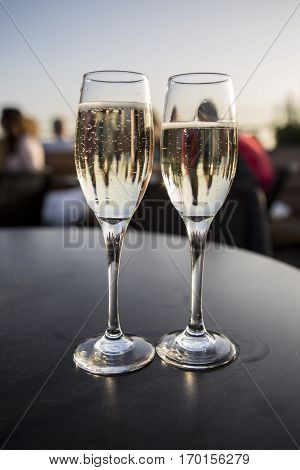 Party and celebration time with champagne flutes in the sunset light