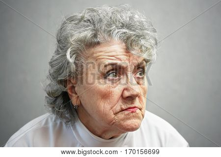 Angry grandmother on a dark grey background.