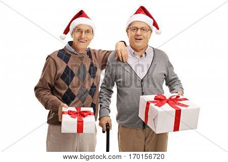 Two elderly men wearing santa hats and holding christmas presents isolated on white background