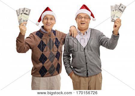 Happy seniors wearing christmas hats and holding bundles of money isolated on white background