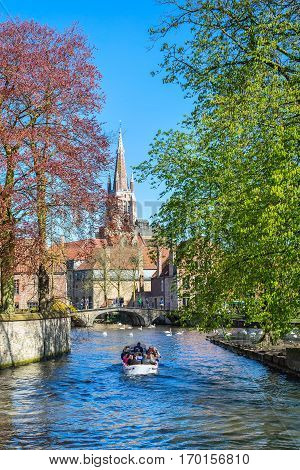 Bruges, Belgium view with canal and bridge, boat, spring trees and church tower
