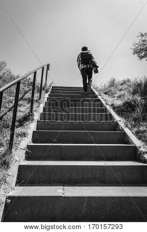 black and white caption of a man walking up stairs