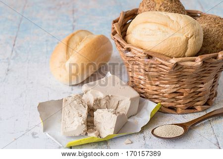 Yeast, fresh and dry granular, next to a wicker basket with fresh bread on a light wooden table.