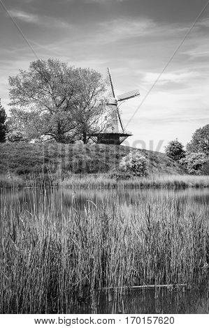 Black and white typical Dutch lspring andscape with a canal and a windmill, Molen de Koe, Veere, The Netherlands