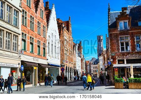 Bruges, Belgium - April 10, 2016: Street view with medieval traditional houses and tower Belfort in popular belgian destination