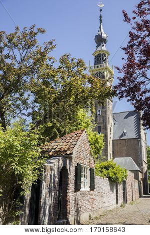 small cobble stone street with town hall's gothic tower in the city of Veere Zeeland province in the Netherlands