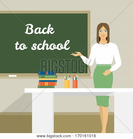Young woman stands near the board. The teacher in the classroom at the table. Back to school
