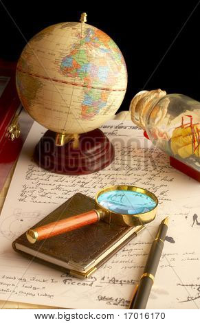 The globe, magnifier with a notebook and the old manuscript.