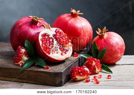 ripe pomegranate with leaves on a wooden board on a dark background