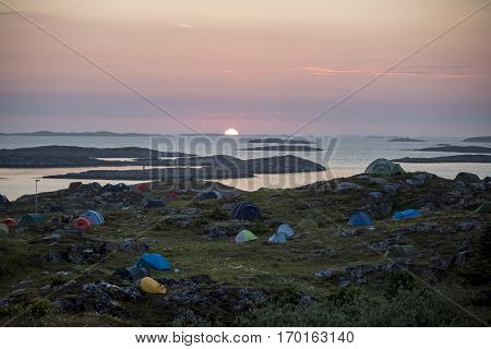 Traena Norway - July 11 2014: at the Traenafestival music festival taking place on the small island of Traena general view over the island and the campsite under the midnight sun