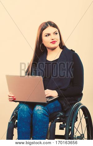 Crippled lady with laptop. Young disabled girl on wheelchair. Health disability internet technology education concept.