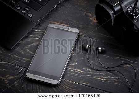 Dark wooden background with gadgets. Laptop, smart phone, photo camera and headset