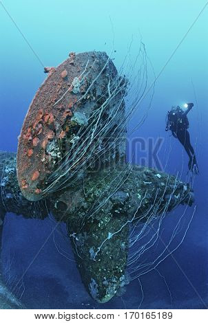 Underwater shoot of female scuba diver swimming near propeller of sunken battleship