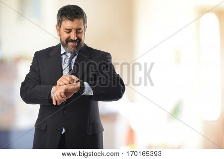 Mature businessman looking at his watch inside an office building