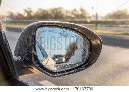 Back View Through Frozen Car Wing Mirror On Motorway
