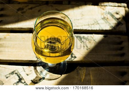 Glass of white Muscat wine with rich yellow ochre copper glow on a wood box in sunrays