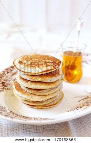 Portion of pancakes with honey on vintage plat