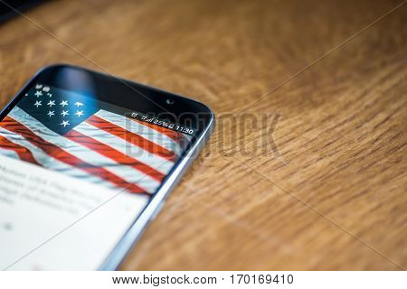 Smartphone On Wooden Background With 5G Network Sign 25 Per Cent Charge And Usa Flag On The Screen