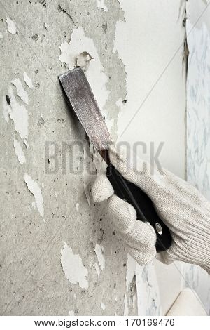 hand in glove removing wallpaper from wall with spatula
