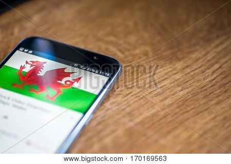 Smartphone On Wooden Background With 5G Network Sign 25 Per Cent Charge And Wales Flag On The Screen
