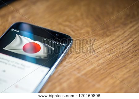 Smartphone On Wooden Background With 5G Network Sign 25 Per Cent Charge And Japan Flag On The Screen