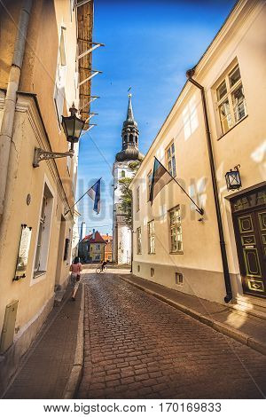 TALLINN ESTONIA - JULE 29 2013: Street of old town of Tallinn with St. Nicholas church in sunny day