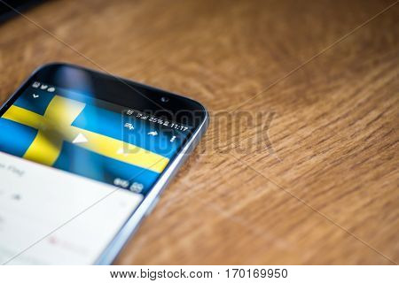 Smartphone On Wooden Background With 5G Network Sign 25 Per Cent Charge And Sweden Flag On The Scree