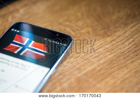 Smartphone On Wooden Background With 5G Network Sign 25 Per Cent Charge And Norway Flag On The Scree