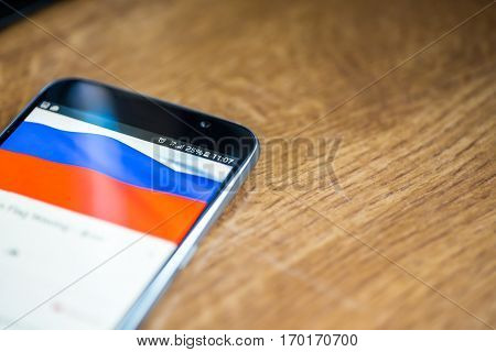 Smartphone On Wooden Background With 5G Network Sign 25 Per Cent Charge And Russia Flag On The Scree
