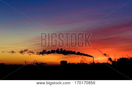 Colourful dramatic sunset in industrial zone of city. Silhouettes of houses and chimneys with smoke. Copy space for your text