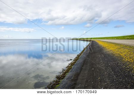 shoreline of Ameland Island with view over the wadden sea with clouds reflecting in water at dawn and a bike lane over a dike