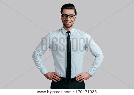 Young and successful. Good looking young man in eyeglasses keeping hands on hip and looking at camera while standing against grey background