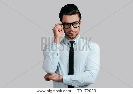 Taking everything seriously. Good looking young man in white shirt and necktie keeping arms crossed and adjusting his eyeglasses while standing against grey background