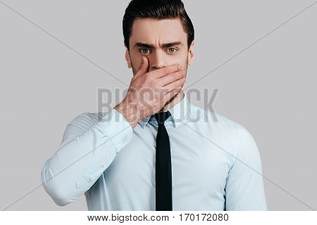 Trying to stop gossiping. Surprised young man in white shirt and tie covering mouth with hand and looking at camera while standing against grey background