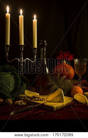 Old style still life with candles, pumkin, cheese, cabbage, likor bottle, lemon slices with black background