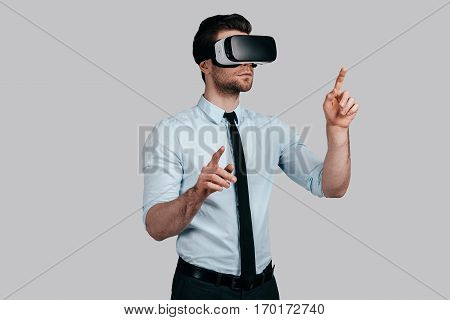 Experiencing virtual reality. Handsome young man in formalwear wearing virtual reality headset and gesturing while standing against grey background