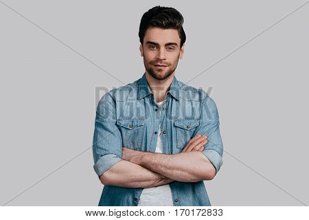 Portrait of confidence. Good looking young man in blue jeans shirt keeping arms crossed and looking at camera while standing against grey background