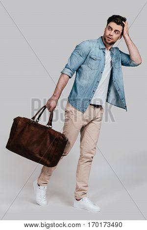 Complementing his style with bag. Full length of handsome young man in casual wear carrying brown leather bag and looking away while standing against grey background