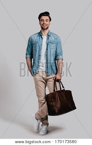 Stylish handsome man. Full length of good looking young man in casual wear carrying brown leather bag and smiling while standing against grey background
