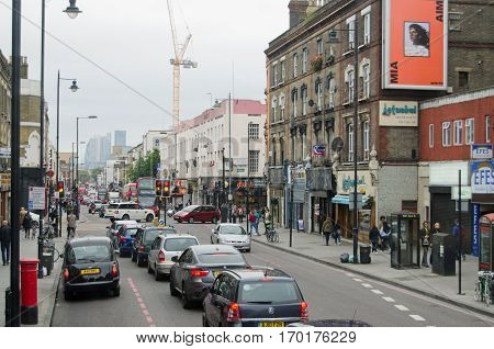 LONDON UK - SEPTEMBER 17 2016: Busy traffic and lots of pedestrians using Kingsland High Street in Hackney in London's East End. The street is one of London's Turkish quarters with the towers of the City of London in the distance.