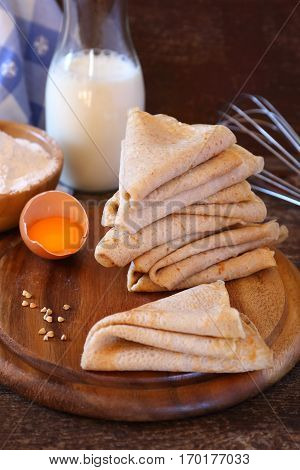 Breton buckwheat crepes and ingredients on wooden table