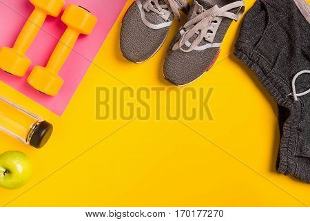 Fitness accessories on yellow background. Sneakers, bottle of water and dumbbells. Top view. Still life. Copy space