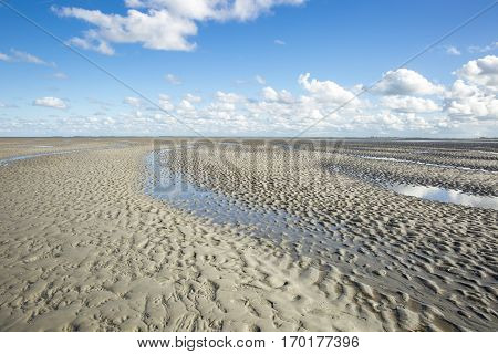Maritime landscape with blue sky white clouds and pattern in the sand Waddenzee - Wadden Sea Friesland The Netherlands