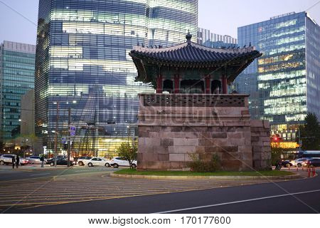SEOUL - NOV 2, 2015: Small arbor with decorated roof on stone postament among road and modern Twin Trees buildings. In Seoul, opened biggest shopping center in Asia